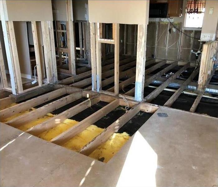 A floor that had the joists and studs removed after a flood